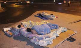 民工雨夜高架桥下铺凉席睡觉